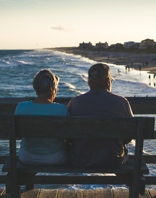 Image to represent an older couple enjoying their pension and benefits by sitting on a bench